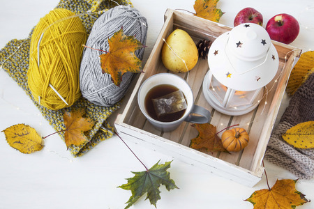 Cosy autumn decor with tea, lantern, leaves, knitting wool and needles, lights on white wooden background