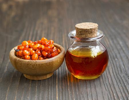 argousier: Seabuckthorn oil bottle with small bowl of seabuckthorn berries