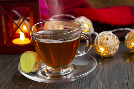 tea cosy: Winter warm ginger tea cup with cosy lantern and lights decorations Stock Photo