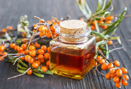 Seabuckthorn oil bottle with berries branches Banco de Imagens