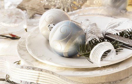 Christmas setting with silver balls and ribbon, festive table,fir tree branches with fork and knife Stock Photo
