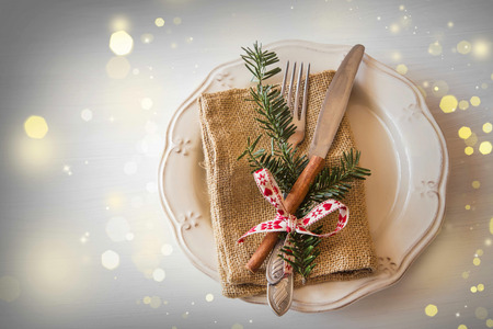 Christmas festive table setting decoration with tableware,fir tree branches, cinnamon stick and ribbon Stock Photo