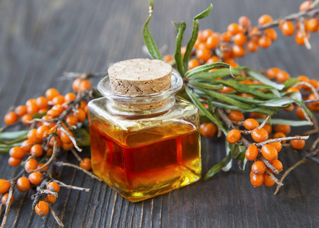 Seabuckthorn oil bottle with berries branches Stock Photo
