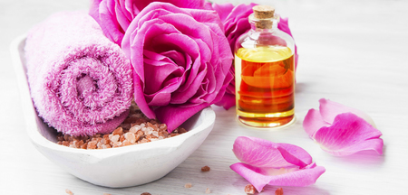 Roses spa setting with bath salt, roses flowers, bath rose oil, still life set