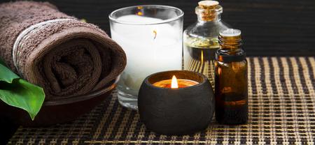 Spa bodegón con toalla, velas, aceite de baño y botella de esencia. Foto de archivo