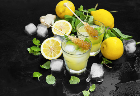 Fresh mojitos cocktails with lemons, fresh mint, ice cubes and sugar sticks on wooden background