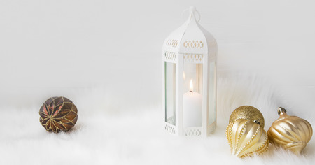White Christmas lantern with white candle and golden balls on white soft faux fur