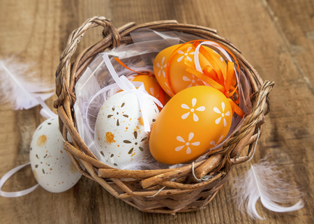 Easter eggs decorated in a basket with feathers on wooden background