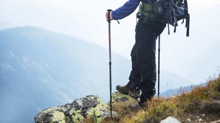 Hiker on a rock on top of mountain with trekking sticks and backpack, mountain valley view, back view Reklamní fotografie