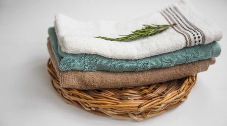 Tas de serviettes de spa, serviettes en coton doux sur plateau en osier nature morte