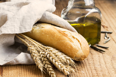 Baguette bread in linen towel with olive oil and ears of wheat Stock Photo