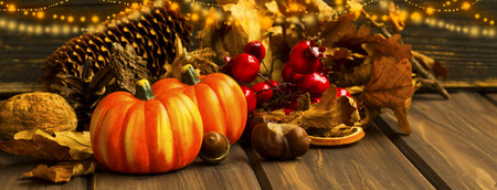Festive autumn pumpkins and decorations with festive lights, fall season deco concept