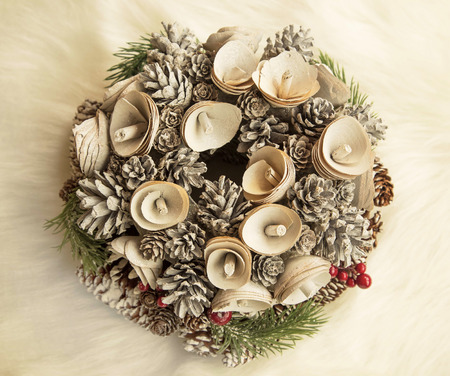 Festive Christmas wreath with cones and wooden flowers, fir tree branches and red berries on faux fur background, festive decoration