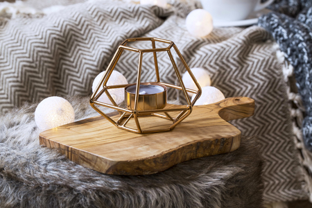 Home deco indoor with candle holder and light bulbs, cozy blanket and faux fur,cozy winter interior details Stock Photo