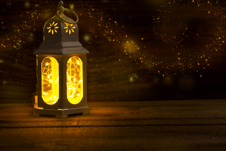 Magic lantern with glowing lights and fireflies on old wooden background