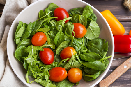 Spring salad closeup with fresh green rocket, spinach leaves and cherry tomatoes , top view