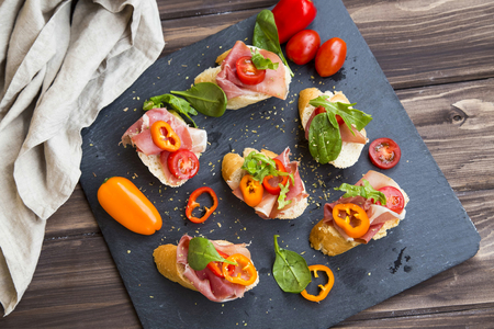 Bruschettas or crostini arrangement with prosciutto ham, green spinach , tomatoes and pepper seasoned with herbs, italian appetizers top view