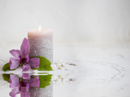Spa still life setting with candle burning and magnolia flower near water , wellness and spa concept  免版税图像