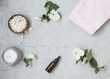 Spa setting flatlay with bath salt, jasmine oil bottle and flowers, towel and natural soap. Spa and wellness still life Standard-Bild