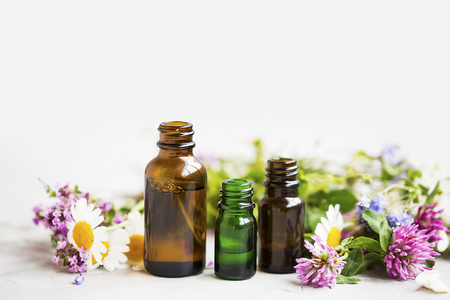 Flowers and herbs essential oil bottles, natural aromatherapy with oils and essences