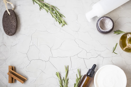 Organic skincare products flatlay with oil bottle, pumice, olive oil, tonic lotion , clay face mask and body butter on clean minimalist grey concrete background with copy space
