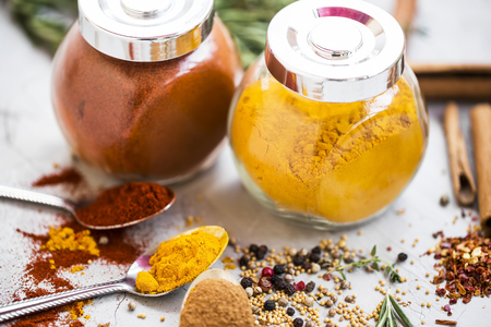 Herbs and spices in jars, powders and seeds, mustard, pepper, paprika , turmeric, rosemary herb, cinnamon and chili flakes