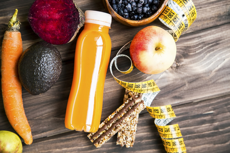 Healthy lifestyle concept with juice bottle, vegetables and fruits with granola muesli bars and measuring tape on wooden board, top view, healthy living fitness concept 写真素材