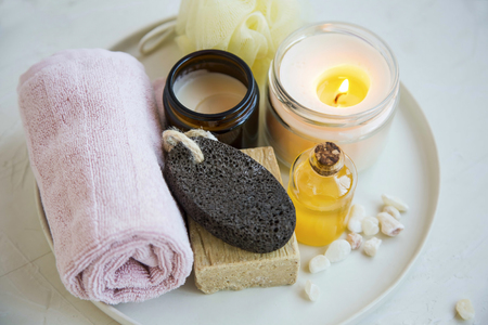 Spa and beauty treatment products  with scented candle, oil, soap, cream and towel, wellness and spa products in a tray, beauty care concept Imagens