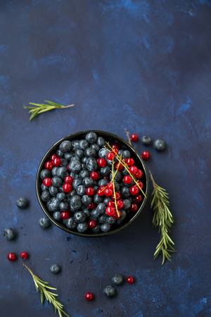 Bowl of healthy organic berries with blueberries and red currants, fresh sweet organic berries top view Stock Photo