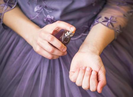 Frau in elegantem lila Kleid, das Parfüm auf ihr Handgelenk auftragt, Nahaufnahme, selektiver Fokus