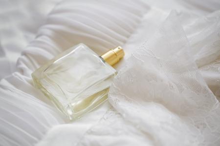 Delicate bride perfume on white lace and silk bride dress, transparent bottle perfume selective focus Banque d'images - 118387674