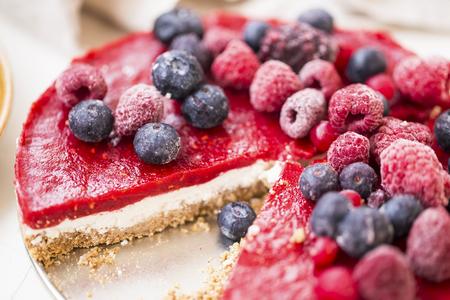 Raw vegan berries tart cake with biscuits, cashew nuts cream cheese, raspberries and blueberries jelly topping, healthy fresh vegan cake with berries Standard-Bild - 118387755