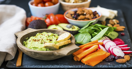 Healthy food selection with guacamole , raw veggies, green leaves spinach, herbs and ingredients, mix of nuts, clean eating, healthy vegan food concept Standard-Bild - 118387762