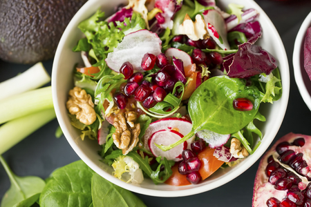 Healthy vegan salad mix in a bowl with nuts, arugula, spinach, radish, tomatoes, pomegranate seeds, top view, healthy clean eating vegan food diet concept Standard-Bild - 118387766