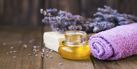Lavender spa oil setting, spa and massage oil still life, lavender towel, flowers , natural soap and lavender oil on wooden background, wooden spa setting and wellness Standard-Bild - 118387767