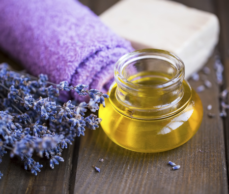 Lavender spa oil setting, spa and massage oil still life, lavender towel, flowers , natural soap and lavender oil on wooden background, wooden spa setting and wellness Standard-Bild - 118387780