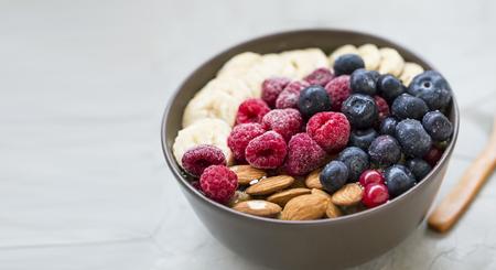 Healthy breakfast with acai bowl, raspberries, blueberries, almonds, bananans , healthy granola or muesli bowl with fresh berries, fresh ingredients Standard-Bild - 118387802