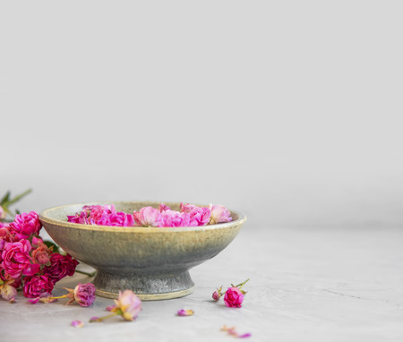 Spa setting with roses and copy space. Rose water bowl for spa and wellness treatments. Rose spa still life Standard-Bild - 118387809