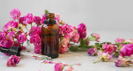 Rose oil. Spa and aromatherapy rose flowers essential oil bottle with pipette Standard-Bild - 118387831