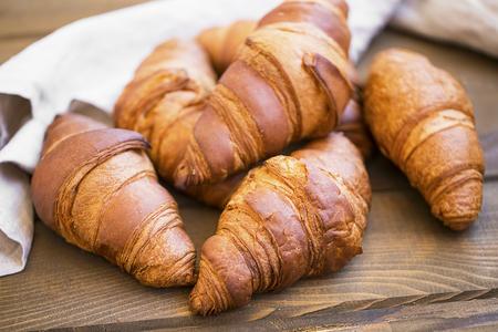 Fresh croisssants buns heap on wooden table, french croissants, fresh crusty breakfast croissants buns Standard-Bild - 118387839