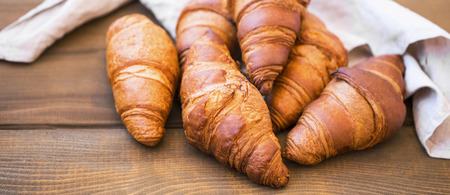 Fresh croisssants buns on wooden table, french croissants, fresh crusty breakfast croissants buns Standard-Bild - 118387840