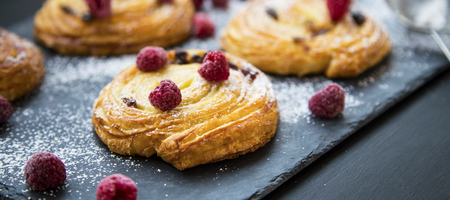 French pastry bun rolls with vanilla and raspberries. Pain aux raisins et vanille, fresh pastry rolls closeup Standard-Bild - 118387842