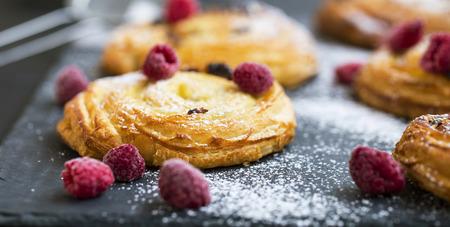 French pastry bun rolls with raisins, vanilla and raspberries. Pain aux raisins et vanille, fresh pastry rolls closeup, french bakery desserts Standard-Bild - 118387847