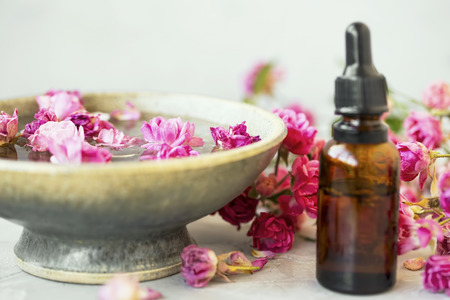 Spa setting with roses. Rose oil bottle with rose water bowl for spa and wellness treatments. Rose spa still life Standard-Bild - 118387852