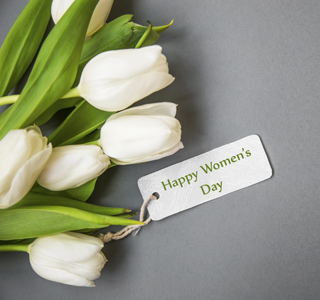 White tulips bouquet with label card , women's day greeting card top view Standard-Bild - 118387893