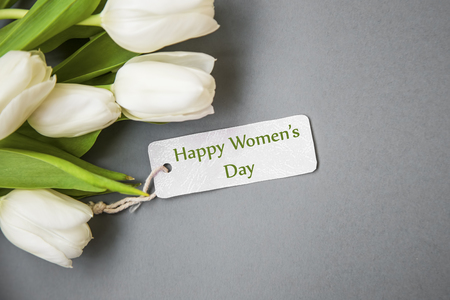 White tulips bouquet with label card , women's day greeting card top view Standard-Bild - 118387895