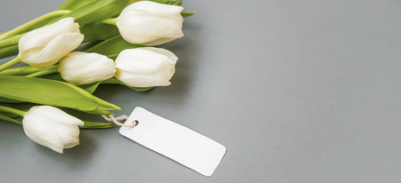 White tulips bouquet with blank label card , women's day greeting card copy space Standard-Bild - 118387897
