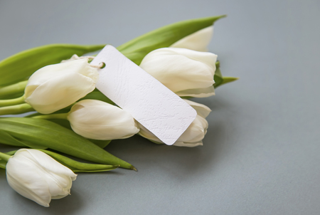 White tulips bouquet with blank label card , women's day greeting card copy space Standard-Bild - 118387901