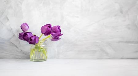 Spring purple tulips bouquet in a vase on grey concrete background, spring flowers bouquet, minimal home decor Standard-Bild - 118387914