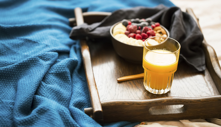 Bed breakfast with glass of orange juice and a bowl of oatmeal with fresh berries, banana and almonds, healthy morning breakfast in wooden tray Standard-Bild - 118917396